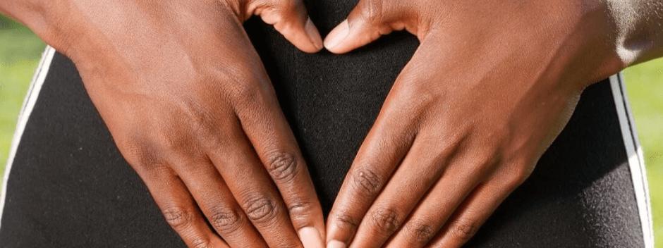 Hände in Herzform auf dem Bauch